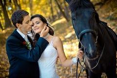 Het sensuele openluchtportret van de romantische mooie jonggehuwden die met paard in het de herfstbos de modieuze bruidegom lopen royalty-vrije stock fotografie