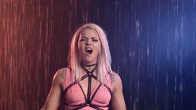 Het sexy aantrekkelijke meisje in een roze bovenkant en een zwaardriem schreeuwt en zingt in de regen suffering Onbeantwoorde lie stock videobeelden