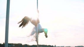 Het sexy aantrekkelijke meisje poledancer voert de geavanceerde trucs van de pooldans bij uit zonsondergang op draagbaar dansend  stock videobeelden