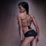 Het sexy Atletische Vrouw Stellen tegen Bruine Muur Royalty-vrije Stock Foto