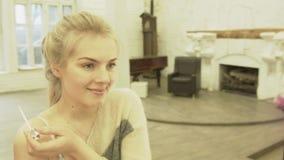 Het sexy blonde schildert lippen bij de spiegel en glimlacht Een mooie jonge vrouw veroorzaakt samenstelling in een grote zaal me stock videobeelden