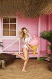 Het sexy en modieuze modelblondemeisje met opblaasbaar roomijs in haar dient modieuze witte zwempaksprongen in en het stellen bij royalty-vrije stock afbeelding