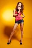 Het sexy gelukkige vrouw dansen opgewekt op geel Royalty-vrije Stock Foto's