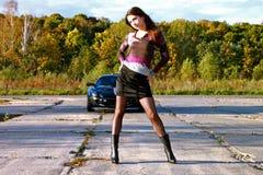 Het sexy heldere meisje bevindt zich voor de auto Stock Foto