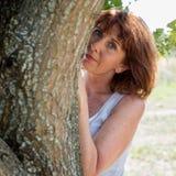 Het sexy het verouderen vrouw verbergen achter een boom voor schoonheidsschuchterheid Royalty-vrije Stock Fotografie
