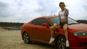 Het sexy jonge blonde zit op een rode auto en likt een lolly stock videobeelden