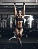 Het sexy jonge geschiktheidsmeisje trekt in de gymnastiek uit Stock Foto's