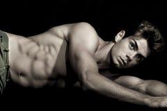 Het sexy jonge mens shirtless liggen op de grond Gymnastiek spierlichaam Royalty-vrije Stock Fotografie