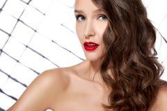 Het sexy jonge mooie meisje met donker krullend haar met rode lippen en blauwe ogen heldere make-up de naakte schouder speels bek Stock Afbeeldingen