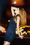 Het sexy jonge mooie vrouw stellen over de achtergrond van de nachtstad Stock Foto