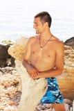 Het sexy Kaukasische geschikte mens stellen in een strand Stock Afbeeldingen