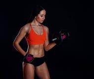 Het sexy meisje die van Nice die training met domoren doen over zwarte achtergrond worden geïsoleerd De atletische jonge vrouw do Stock Foto