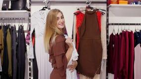 Het sexy meisje, lange, mooie blonde vrouw kiest kleren in de opslag, bewonderend voor een spiegel, glimlachen stock videobeelden