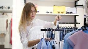 Het sexy meisje, lange, mooie blonde vrouw kiest kleren in de opslag Het winkelen in een modieuze kledingsopslag Langzame Motie stock video