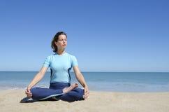 Het sexy meisje in met de benen over elkaar yogalotusbloem stelt bij strand Royalty-vrije Stock Fotografie