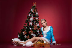 Het sexy Meisje van de Sneeuw zit op rood met nieuwe jaarboom Royalty-vrije Stock Foto's