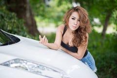 Het sexy meisje in zwart vest stelt op kapauto royalty-vrije stock fotografie