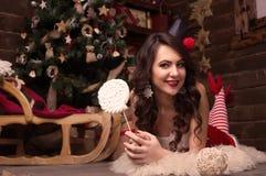 Het sexy model kleedde zich als Kerstman met een zwarte kroon en een groot suikergoed Royalty-vrije Stock Afbeeldingen