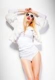 Het sexy model van de maniervrouw gekleed in wit die zonnebril stellen dragen betoverend mooi in de studio stock foto