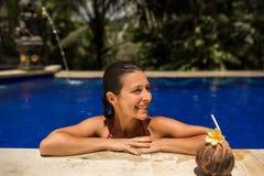 Het sexy slanke donkerbruine jonge vrouwelijke stellen met verse kokosnoot in pool met kristal blauw water De koninklijke tropisc stock afbeelding