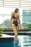 Het sexy slanke vrouwelijke stellen tussen groene installaties in pool op dak met cityscape Luxevakantie in Azië stock afbeeldingen