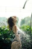 Het sexy slanke wijfje in zwempak neemt douche in zwembad tussen groene struiken op dak met stads scape achtergrond royalty-vrije stock foto