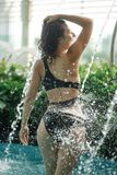 Het sexy slanke wijfje in zwempak neemt douche in zwembad tussen groene struiken op dak met stads scape achtergrond royalty-vrije stock fotografie