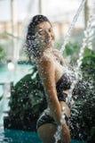 Het sexy slanke wijfje in zwempak neemt douche in zwembad tussen groene struiken op dak met stads scape achtergrondluxe royalty-vrije stock afbeeldingen