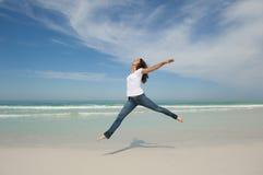 Het sexy vrouw springen gelukkig bij strand Stock Afbeeldingen