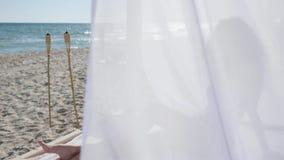 Het sexy wijfje met krullen in strandbungalow, witte doek, wind ontwikkelt haar, tropisch strand, op achtergrondoverzees en zand stock video