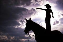 Het Silhouet dat van de cowboy zich op Paard bevindt Royalty-vrije Stock Foto's