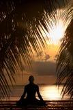 Het silhouet dat van de mens yogaoefening doet Stock Afbeeldingen