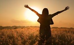 Het silhouet dat van de vrouw op de zomerzon wacht Stock Afbeelding