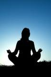 Het silhouet dat van de vrouw yoga maakt Stock Foto