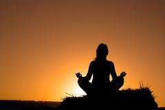 Het silhouet dat van de vrouw yoga maakt stock afbeeldingen