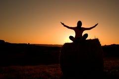 Het silhouet dat van de vrouw yoga maakt royalty-vrije stock afbeeldingen