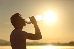 Het silhouet drinkwater van de geschiktheidsmens van een fles Stock Foto's