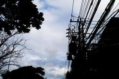 Het silhouet, elektrische pool met heeft transformatoren één Stock Afbeeldingen