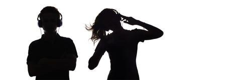 Het silhouet van cijferstieners in hoofdtelefoons die aan muziek luisteren, de kerel en het meisje dansen met omhoog handen, het  stock foto's