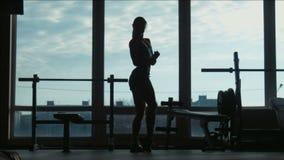 Het silhouet van de aantrekkelijke vrouw stelt en toont spieren in een gymnastiek stock footage