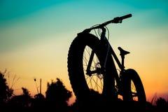 Het silhouet van de bergfiets op mooie zonsondergang Stock Afbeeldingen