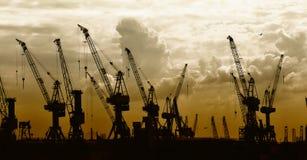 Het silhouet van de bouw van kranen op zonsondergang   Stock Fotografie