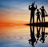 Het silhouet van de familie op zonsonderganghemel. Stock Foto