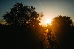 Het silhouet van de fietser op bergfiets bij zonsondergang stock afbeelding