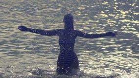 Het silhouet van de jonge slanke gelukkige vrouw die zich in de overzeese en van het plonsenwater handen bevinden Langzame Motie stock video