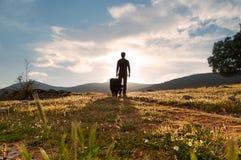 Het silhouet van de mens en zijn gelovige metgezel bij zonsondergang in de weide bloeien Stock Fotografie