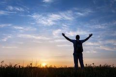 Het silhouet van de mens met wapens hief omhooggaande en mooie hemel op Royalty-vrije Stock Afbeelding