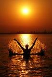 Het silhouet van de mens op zonsondergang Stock Afbeelding
