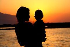 Het silhouet van de moeder en van de baby stock foto's