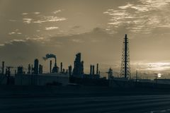 Het silhouet van de olieraffinaderij bij zonsopgang Stock Foto's